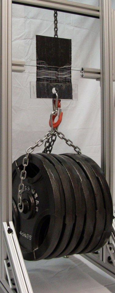 A 4x4 inch Geckskin pad holding 300 lbs on glass